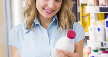 Femeie priveste eticheta produsului scrisa in limba engleza