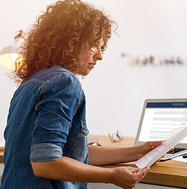 Woman at computer with document in hand