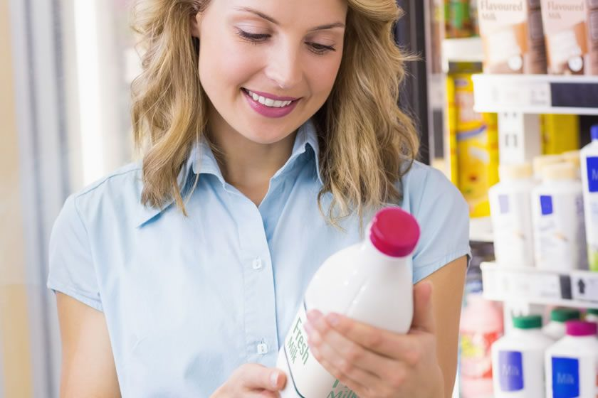 Woman looks at the product label written in English